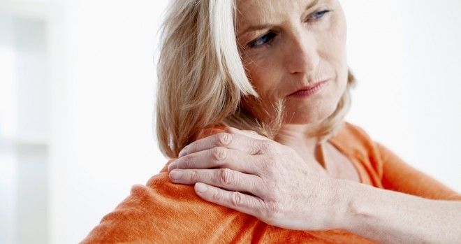 A woman rubbing her shoulder with her left hand