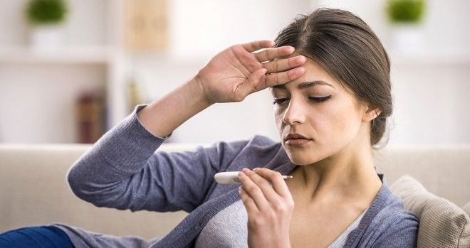 A woman with her hand on her forehead and a thermometer checking for fever