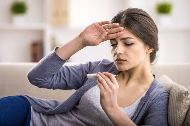 Woman checks herself for a fever with thermometer