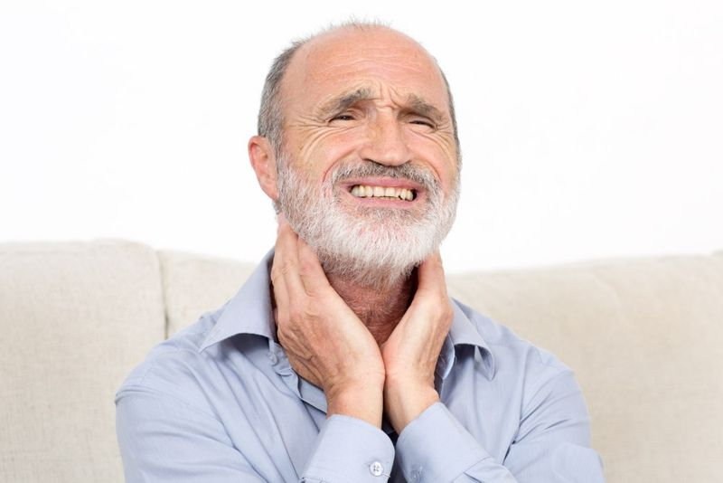 Man holds hands on either side of his neck to feel lymph nodes