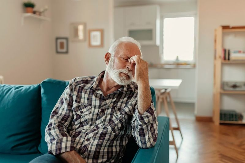 older man with hand on twitching eyes