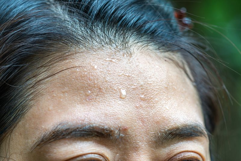 woman's forehead close up sweating