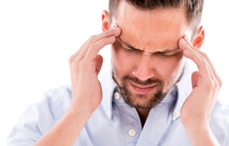 man with a headache with his fingers on his temples
