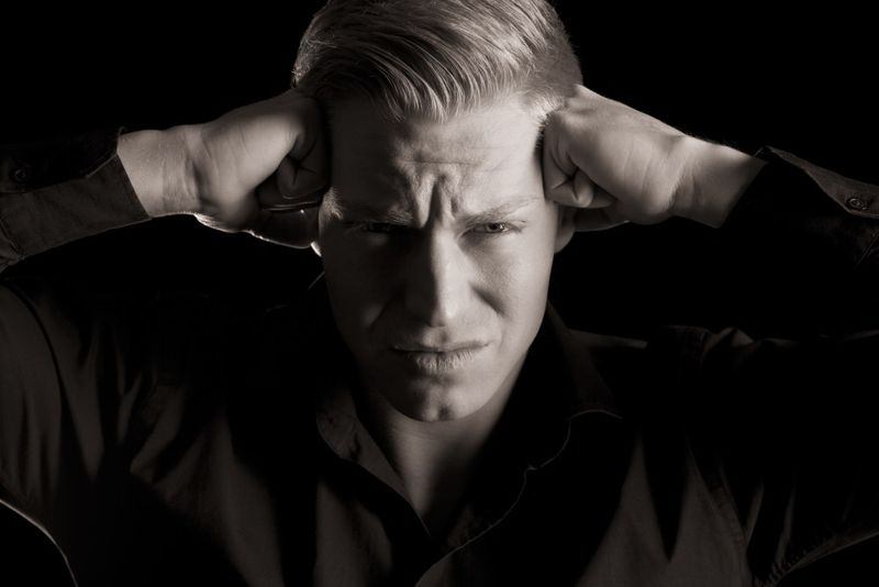 man with frustrated expression on his face holding his head with his hands