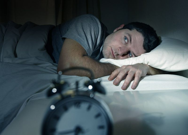 man laying in bed with eyes open