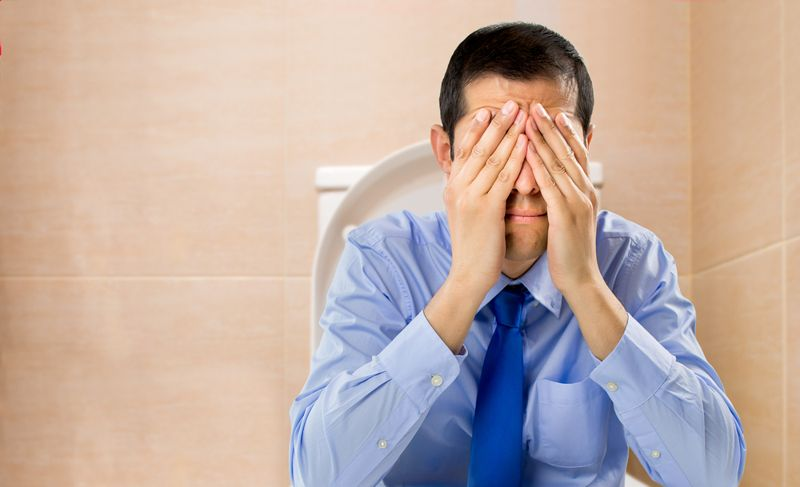 man on toilet with hands over his eyes