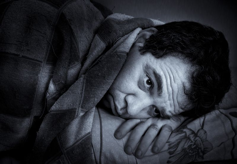 man in bed not being able to sleep