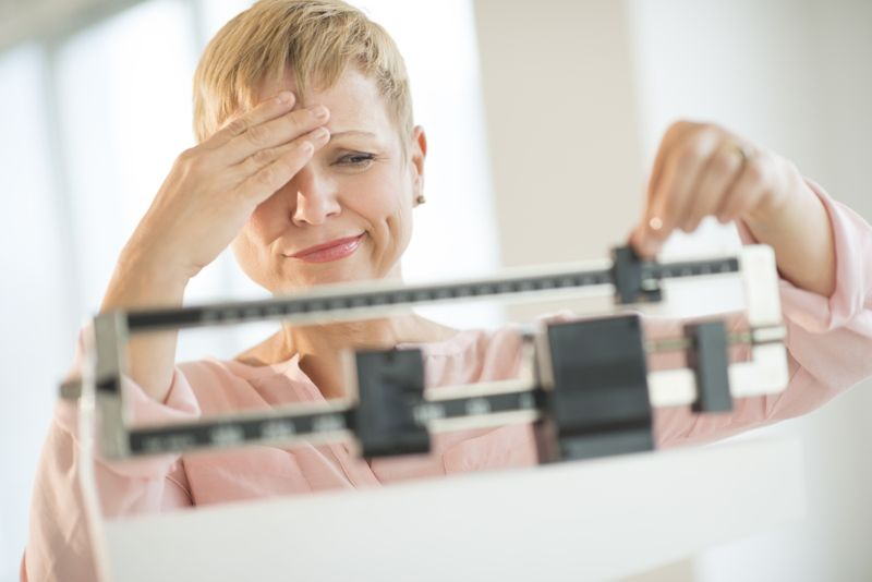 woman on the scale looking unhappy