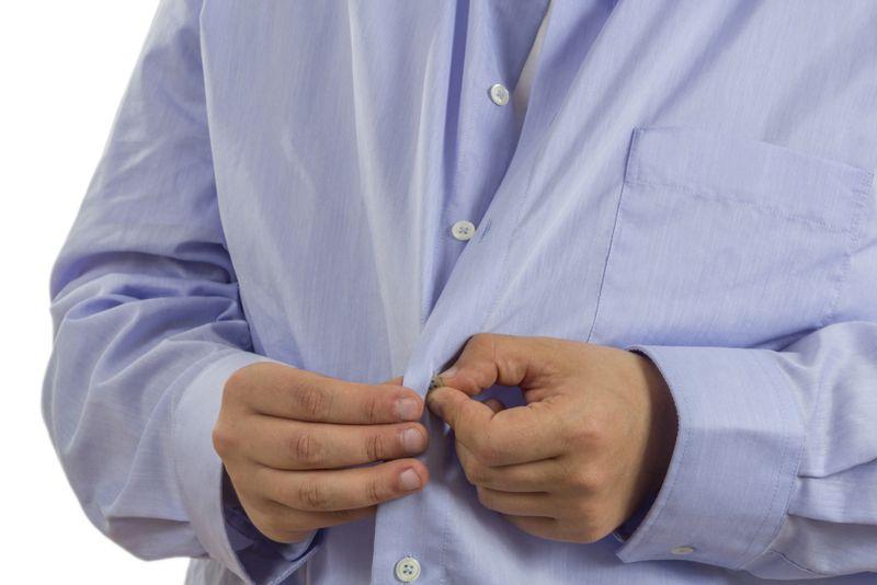 man buttoning up a blue dress shirt