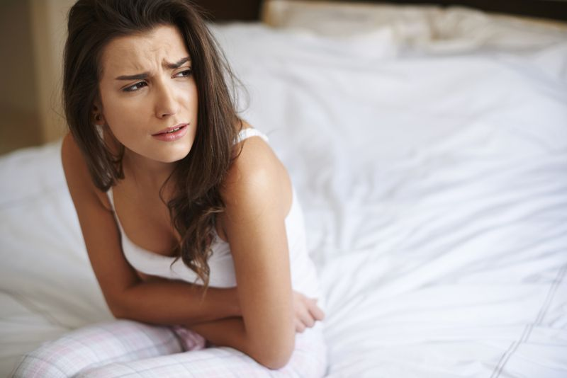 women sitting on a bed leaning over in pain