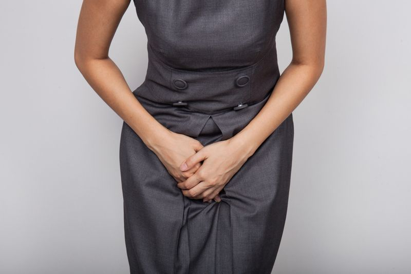 Woman's torso with her hands over her bladder