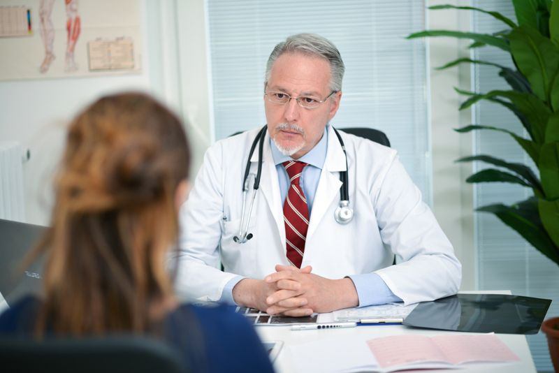 A doctor speaking to a woman about her symptoms