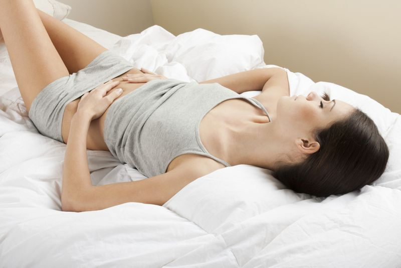 Woman laying on her back in bed with her hands on her lower stomach