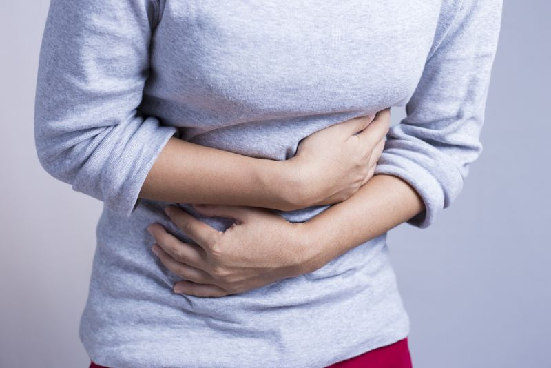 Person in a grey sweater holding their abdomen in pain