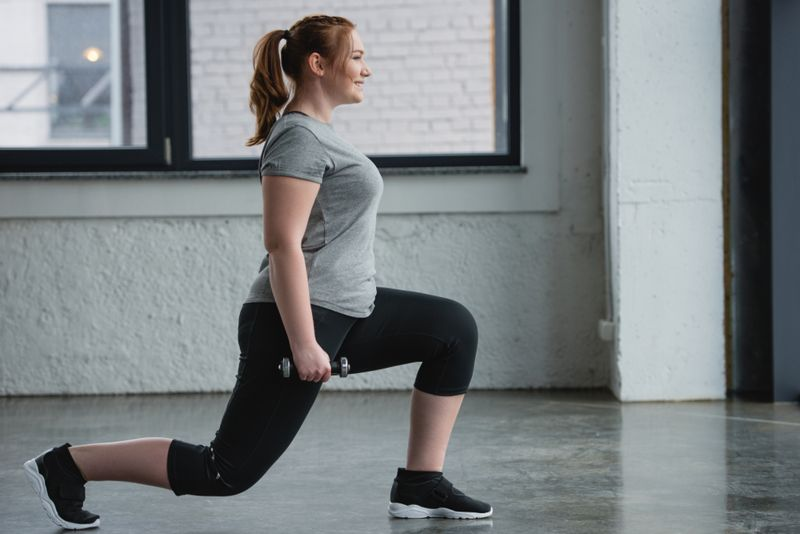 Woman leans forward stretching legs while holding weights