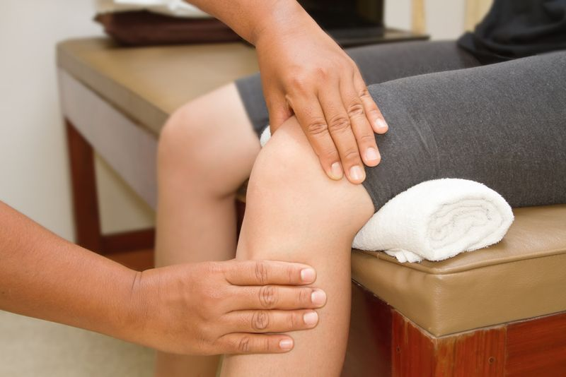 doctor inspecting patient's knee joint