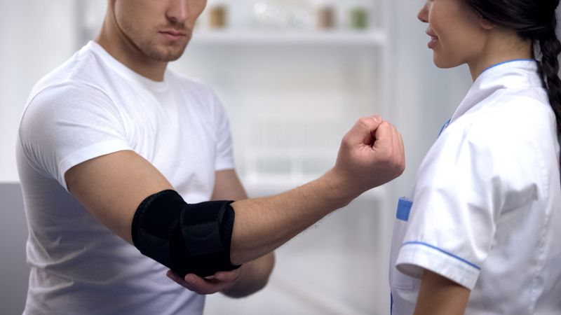 man showing elbow brace to doctor