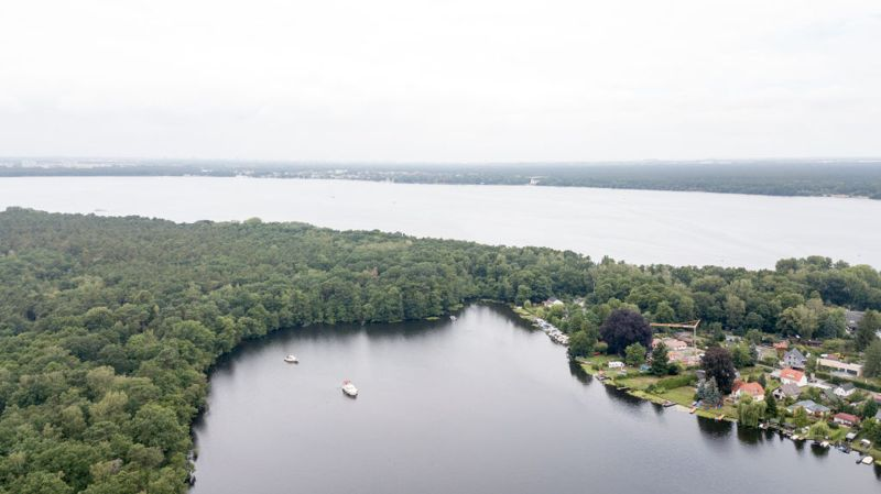 """Berlin, Germany - July 10, 2018: Aerial view of the Müggelsee (Lake) near Berlin. In front you can see the """"Kleine Müggelsee"""", in the back the huge """"Große Müggelsee"""". It is the largest of the Berlin lakes by area, with an area of 7.4 square kilometres."""