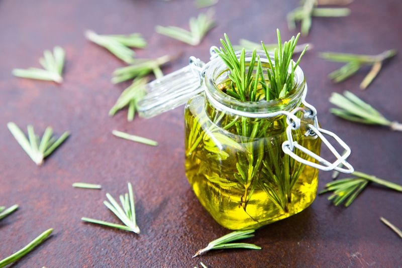 osemary essential oil jar glass bottle and branches of plant rosemary with flowers on rustic background