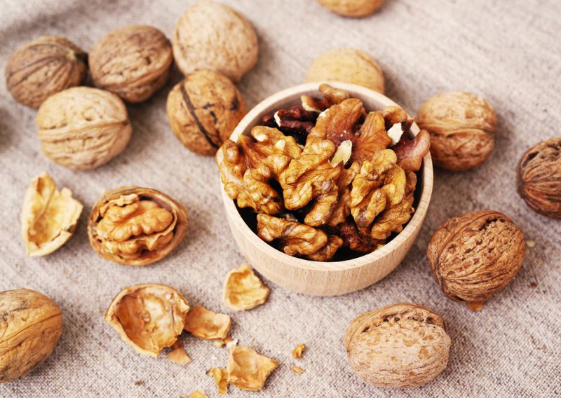 Walnut kernels in a wooden bowl and whole walnuts on table.
