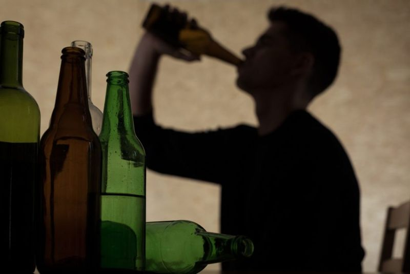 man excessively drinking alcohol