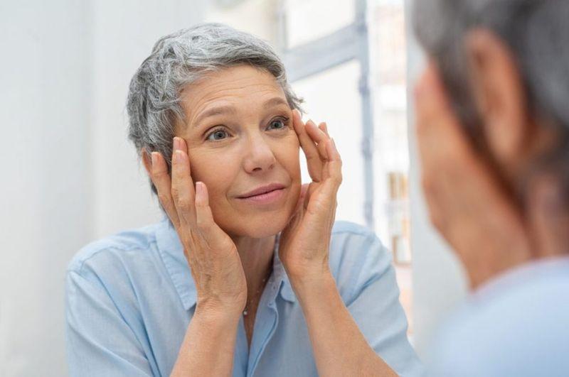 woman mirror skin aging