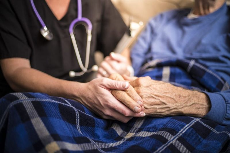 Healthcare professional holding a patient's hands