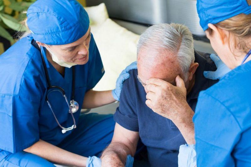 Man feeling unwell helped by nurses