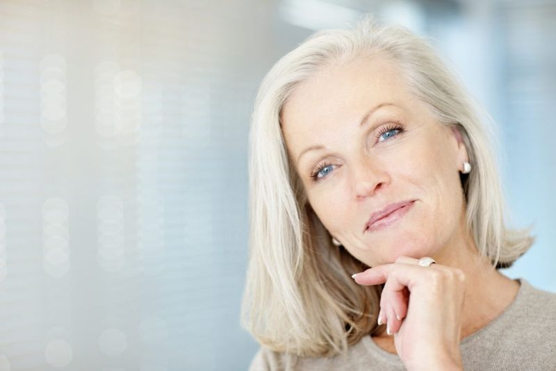 Close-up portrait of a beautiful mature woman with hand on chin giving you a warm smile