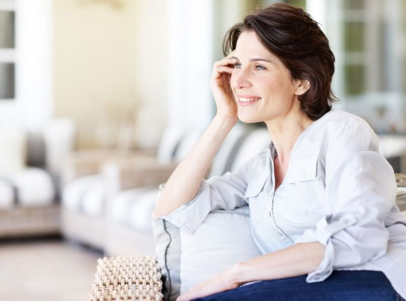 A serene woman sitting on couch in her home