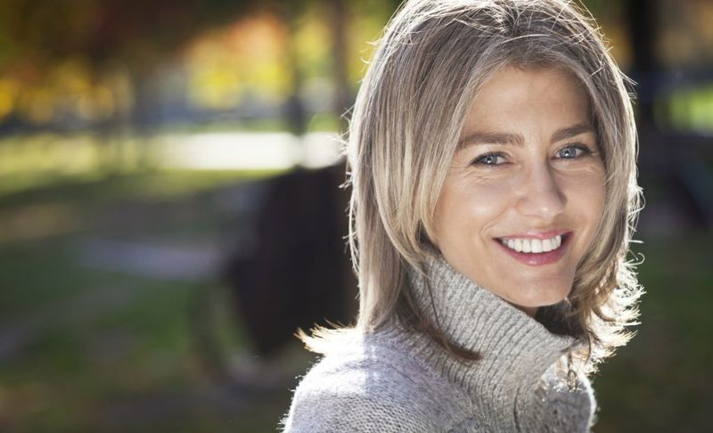 Portrait Of A Mature Woman Smiling At The Camera. Outside. Gray hairs.