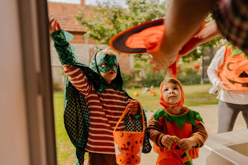 Photo of two little costumed boys on a trick or treat adventure in their neighborhood.