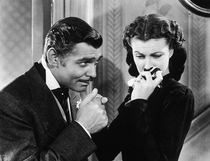 American actor Clark Gable (1901 - 1960) in his role as Rhett Butler kissing the hand of a tearful Scarlett O'Hara, played by Vivien Leigh in 'Gone With The Wind'.