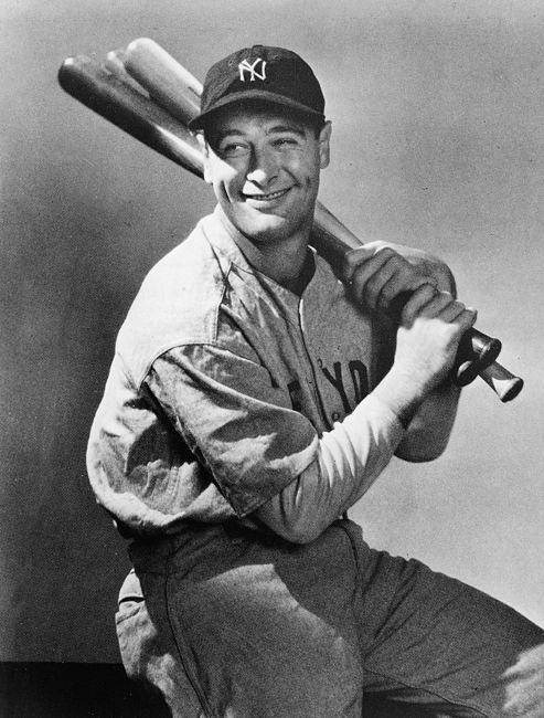 Portrait of New York Yankees first baseman, Lou Gehrig (1903 - 1941), seated with three baseball bats over his shoulder, circa 1930s.