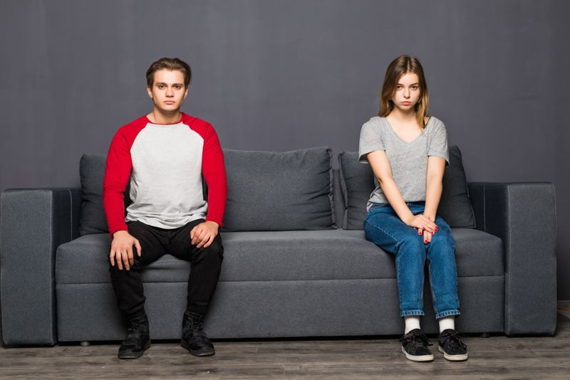 Young couple sitting on sofa separate isolated on gray