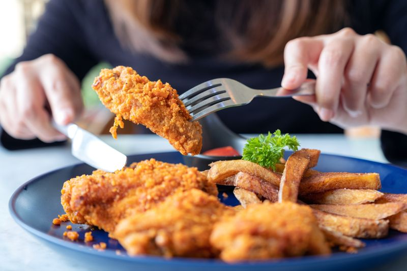 Closeup image of a woman using knife and fork to eat fried chicken and french fries in restaurant
