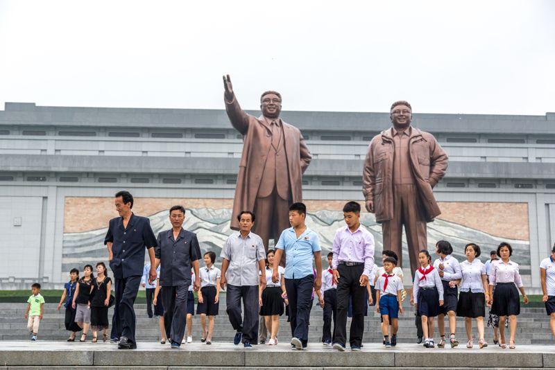 Locals walking in front of a big statue in Pyongyang, North Korea capital on a cloudy day