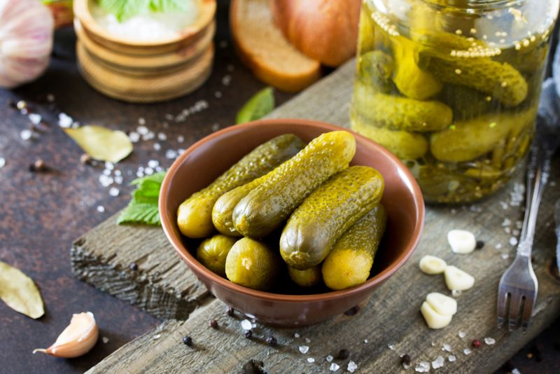 Pickles with mustard and garlic on a stone background