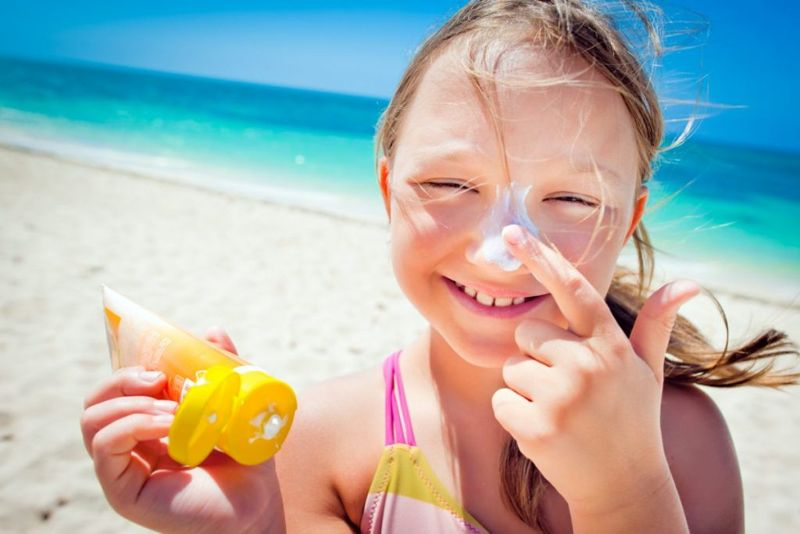 Young girl applying sunscreen to nose