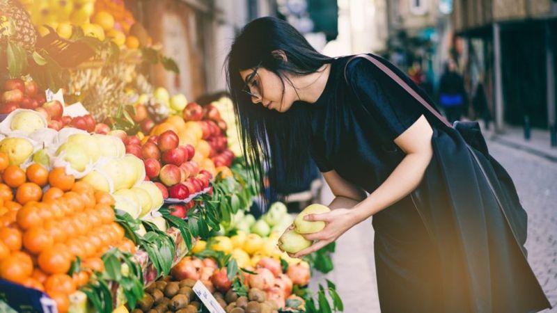 woman buying fresh fruit