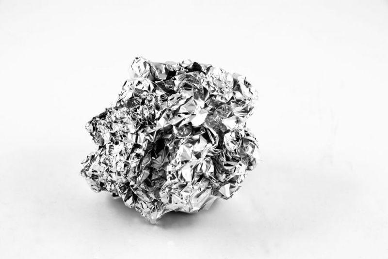 Aluminum reacts chemically to remove tarnish.