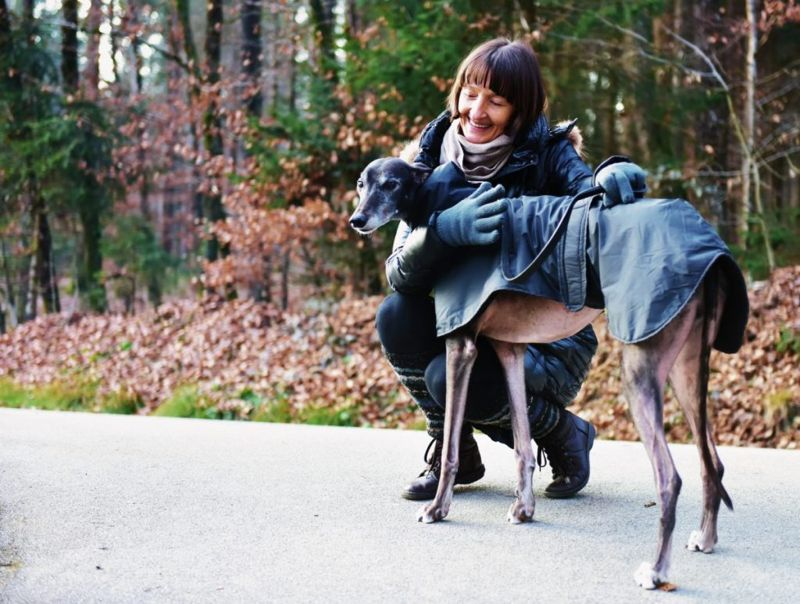 Woman with greyhound in jacket
