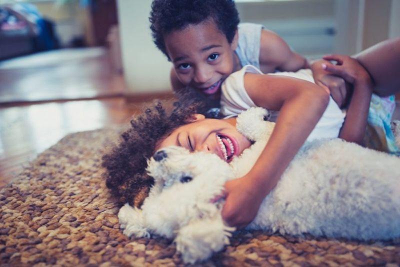 Children cuddle dog
