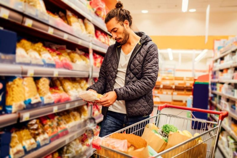 Young bearded man in groceries shopping. He is choosing pasta and reading nutrition label on product. Location released.
