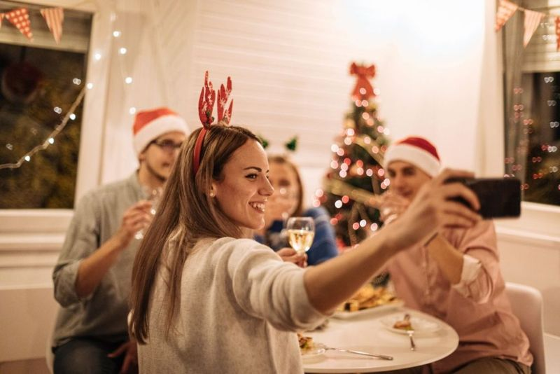 Beautiful woman taking selfie during the dinner near christmas tree