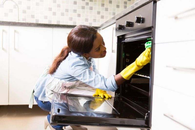 african woman cleaning stove in the modern kitchen