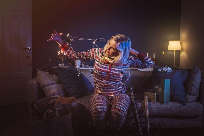Christmas woman at home with christmas lights tangled