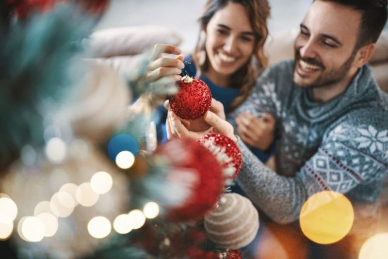 Young couple decorating a Christmas tree