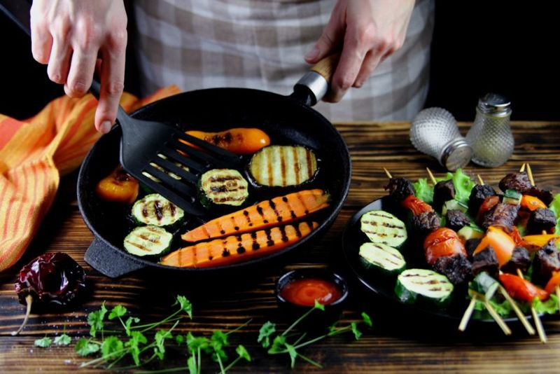 Chef preparing vegetables in a cast iron skillet
