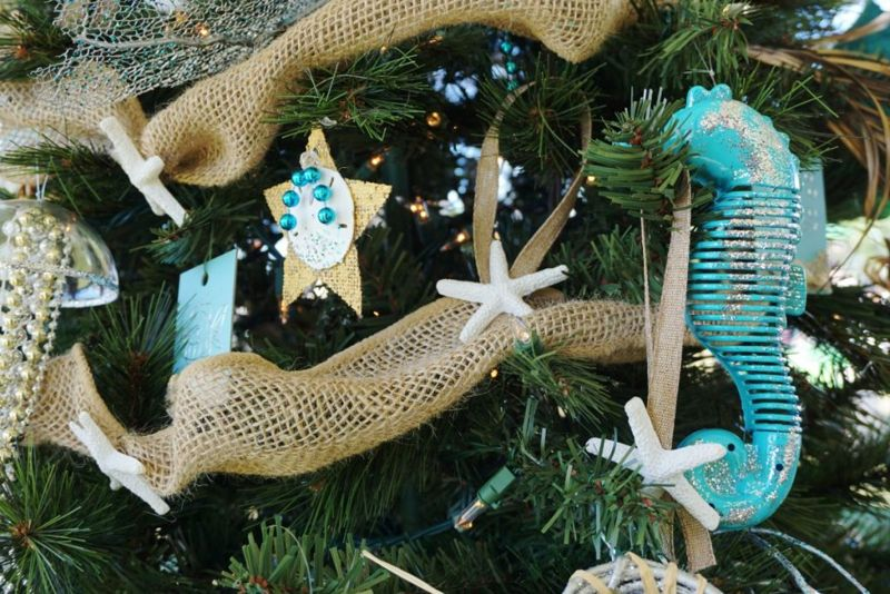 Christmas tree decorated with beige, blue, white, and nautical marine themed ornaments